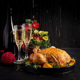 Gebackener truthahn oder huhn. der weihnachtstisch wird mit einem truthahn serviert, der mit hellem lametta dekoriert ist. gebratenes huhn. sitzordnung bei tisch. weihnachtsessen.