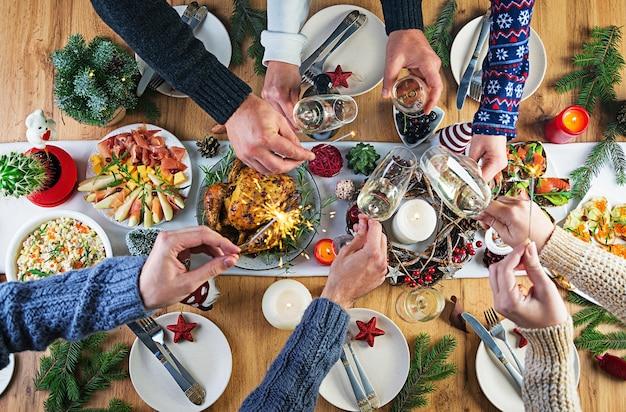 Gebackener truthahn. weihnachtsessen. der weihnachtstisch wird mit einem truthahn serviert, der mit hellem lametta und kerzen dekoriert ist. brathähnchen, tisch. familienessen. draufsicht, hände im rahmen