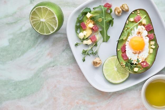 Gebackenes avocadoboot mit schinkenwürfeln, wachtelei und käse diente mit grünem rucolasalat auf marmor