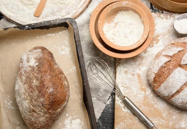 Gebackenes brot auf dem tisch und zutaten, küchenutensilien liegen in der nähe, draufsicht