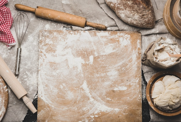 Gebackenes brot, weißes weizenmehl, hölzernes nudelholz und altes schneidebrett auf einem tisch, draufsicht