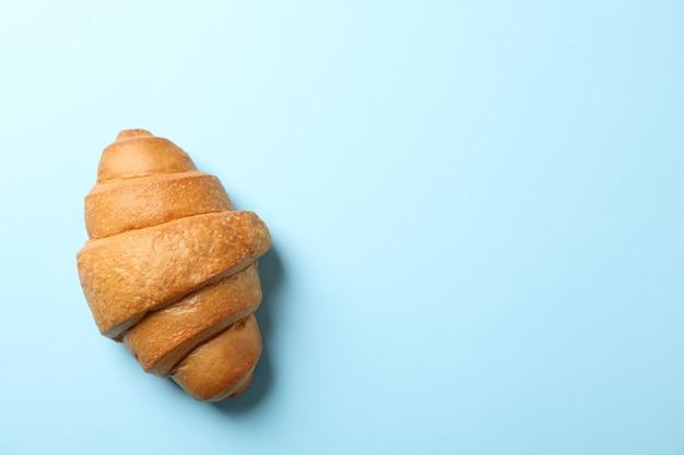 Gebackenes croissant auf blauem hintergrund, draufsicht