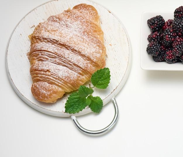 Gebackenes croissant bestreut mit puderzucker und brombeeren in einer schüssel auf einem weißen tisch