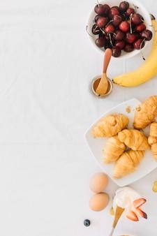 Gebackenes croissant mit früchten; ei und joghurt auf weißem hintergrund