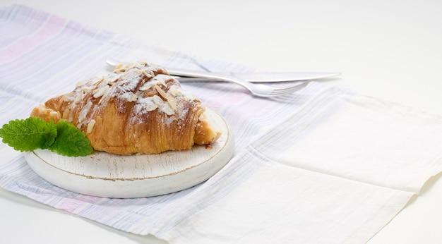 Gebackenes croissant mit zucker bestreut auf holzbrett, weiße leinenserviette