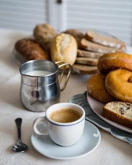 Gebackenes essen mit tee und milch auf dem tisch
