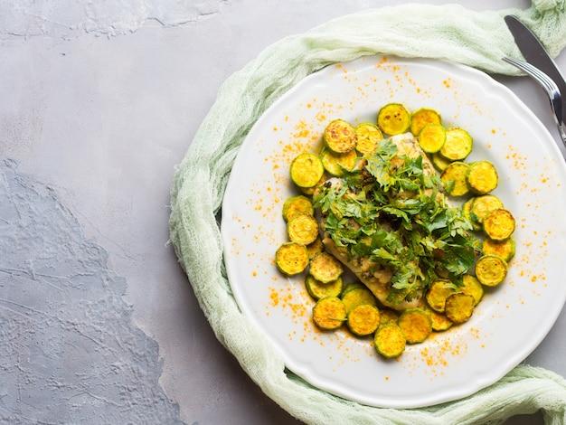 Gebackenes fischfilet auf lager mit mandelpetersilienbelag und gelbwurzzucchini auf weißer platte. teller der gesunden diät