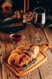 Gebackenes fleisch mit preiselbeersauce und einem glas wein auf dem weihnachtstisch.
