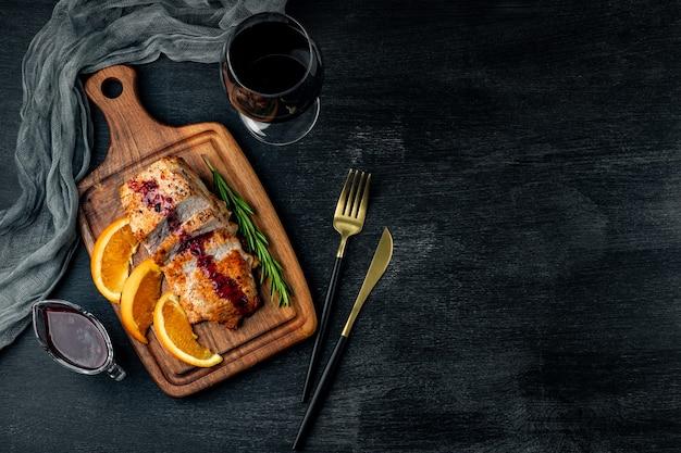 Gebackenes fleisch mit preiselbeersauce und einem glas wein auf schwarzer draufsicht