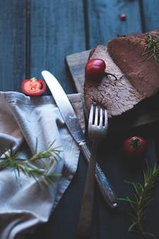 Gebackenes fleisch mit rosmarin und paprika. steak. rindfleisch. abendessen für männer. dunkles foto. schwarzer hintergrund. holzbrett.