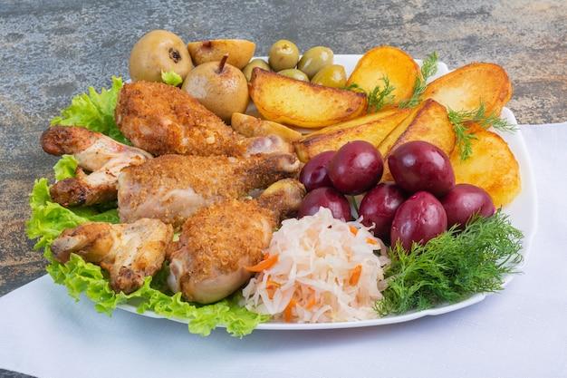 Gebackenes fleisch und kartoffeln neben konserviertem gemüse auf einem teller auf einem tuch.