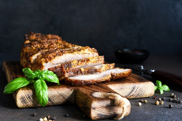 Gebackenes gekochtes schweinefleisch. gebackene fleischscheibe mit knoblauch und gewürzen auf einem holzbrett.