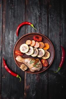 Gebackenes gemüse auf einem teller, ein stück fleisch auf dem grill gekocht