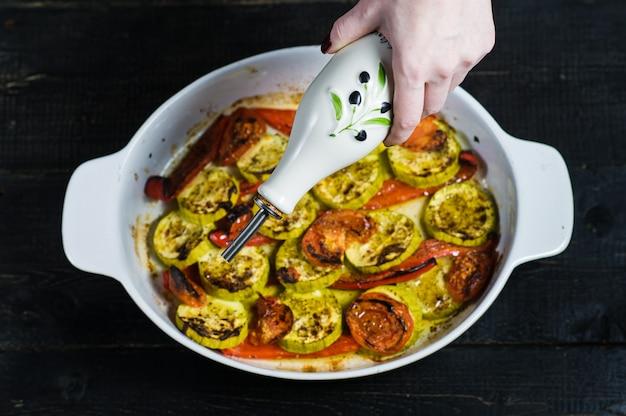 Gebackenes gemüse in auflaufform, zucchini, paprika und zucchini.