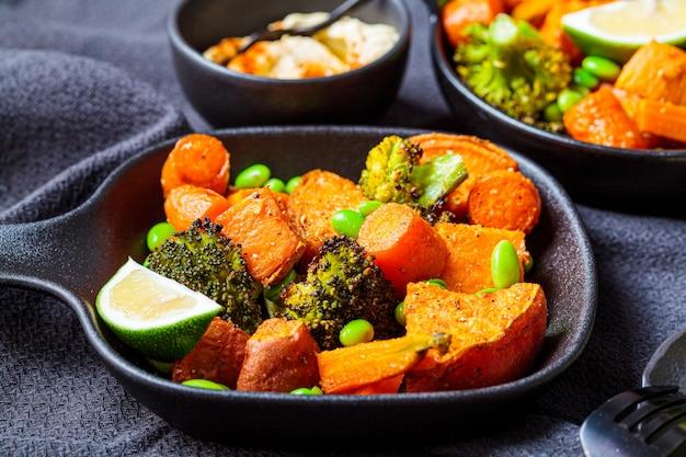 Gebackenes gemüse in gusseisernen pfannen, dunkler hintergrund. gebackene süßkartoffeln, brokkoli, karotten und bohnen.