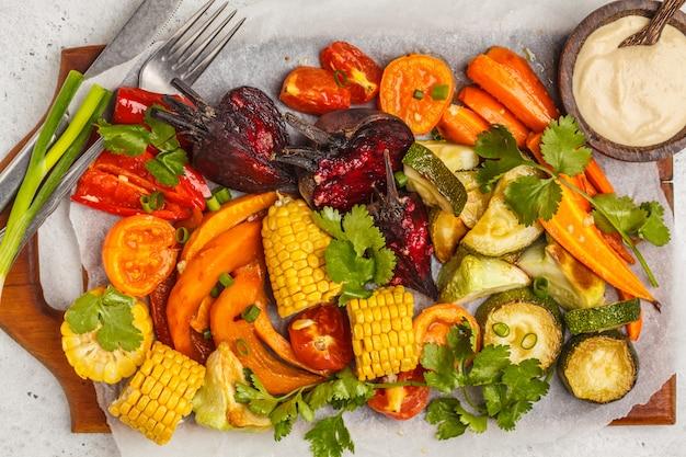 Gebackenes gemüse: kürbis, rote rüben, karotten, paprika, zucchini und mais auf holzbrett.