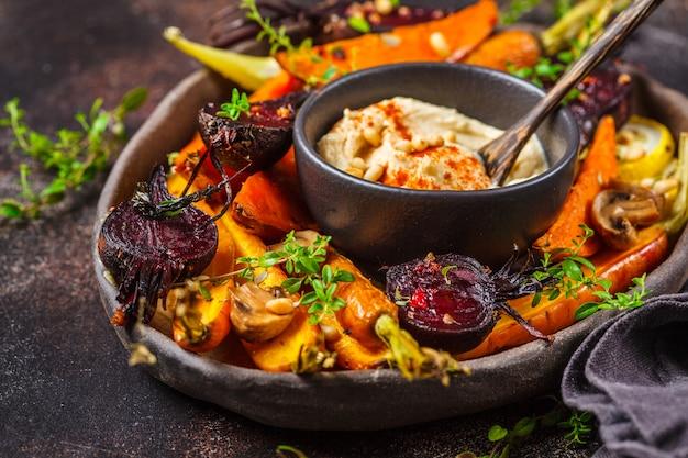 Gebackenes gemüse mit hummus in einem dunklen teller.