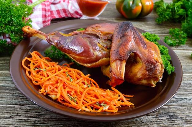 Gebackenes hähnchen mit goldener knuspriger kruste und frischem karottensalat auf einer keramikplatte.