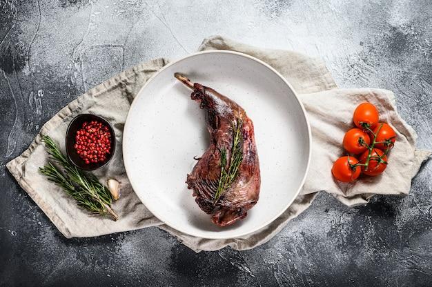 Gebackenes hasenbein mit kräutern, serviert auf textilserviette. bio-fleisch. draufsicht.