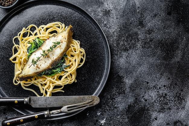 Gebackenes heilbutt-fischsteak und spaghetti-nudeln mit spinat.