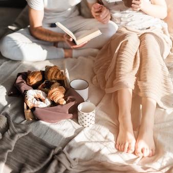 Gebackenes hörnchen und tasse kaffee mit den paaren, die auf bett sitzen