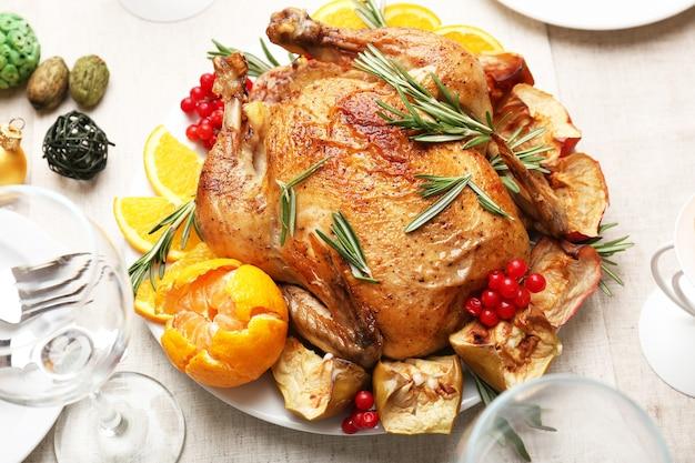 Gebackenes hühnchen für festliches abendessen. thanksgiving-tischdekoration