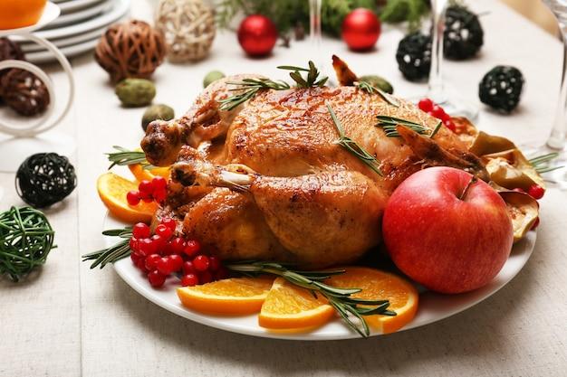 Gebackenes hühnchen für festliches abendessen. tischdekoration zu weihnachten
