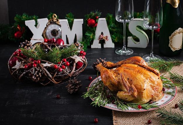 Gebackenes hühnchen oder truthahn. der weihnachtstisch wird mit truthahn serviert, der mit hellem lametta dekoriert ist. gebratenes huhn, tisch. weihnachtsessen. sitzordnung bei tisch. ansicht von oben, oben