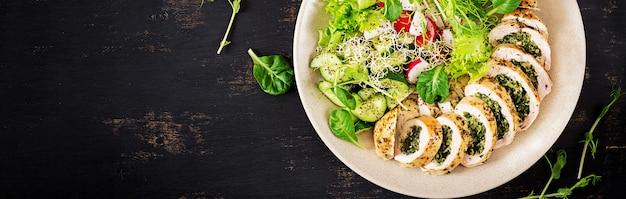 Gebackenes hühnerbrötchen mit spinat und käse auf platte.