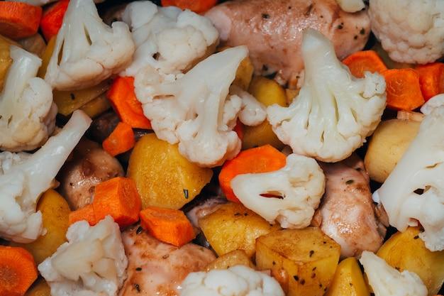 Gebackenes hühnerfleisch mit kartoffeln und gemüse karotten und blumenkohl