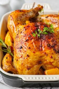 Gebackenes huhn mit gewürzen, preiselbeeren, orange und zwiebeln in einer glasschale.
