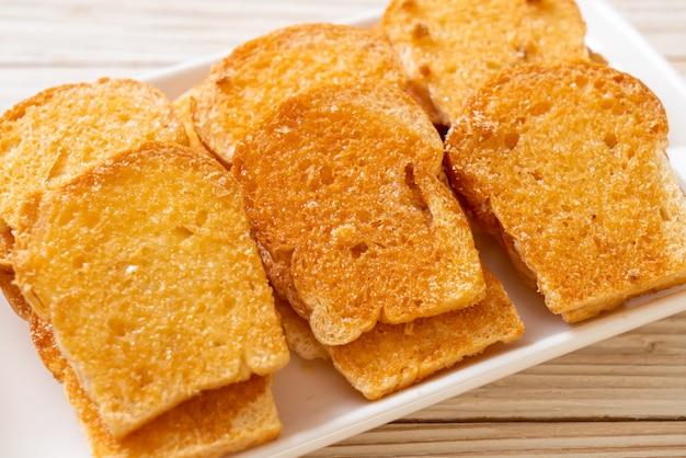 Gebackenes knuspriges brot mit butter und zucker auf teller