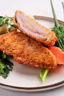 Gebackenes kotelett angefüllt mit dem schinken und käse, abgedeckt mit dem geschmolzenen käse getrennt auf weiß
