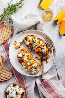Gebackenes kürbissandwich mit dorblu-käse mit blauschimmel, honig und thymian auf einem konkreten alten hellen hintergrund. ansicht von oben