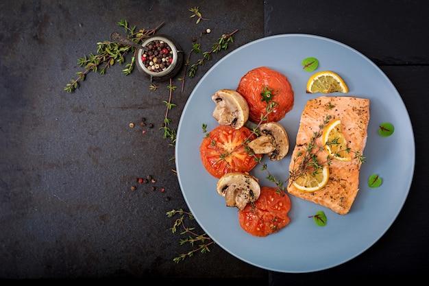 Gebackenes lachsfischfilet mit tomaten, pilzen und gewürzen. diätmenü.