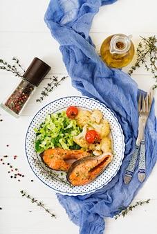 Gebackenes lachssteak mit blumenkohl, tomaten und kräutern. richtige ernährung. draufsicht