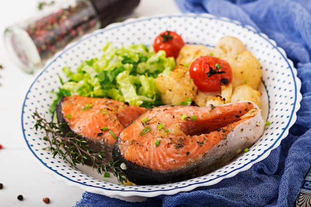 Gebackenes lachssteak mit blumenkohl, tomaten und kräutern. richtige ernährung.