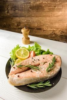 Gebackenes lachssteak mit salat, zitrone und gemüse. rotes fischsteak nahaufnahme.