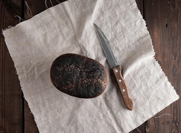 Gebackenes roggenbrot liegt mehl auf textiltuch, hölzerne alte tabelle