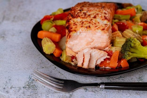 Gebackenes saftiges lachsfilet mit gedämpftem gemüse auf schwarzem teller. gesundes essen.
