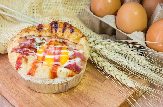 Gebackenes sandwich mit ei, käse und schinken. warmes frühstück brötchen mit flüssigem ei, schinken