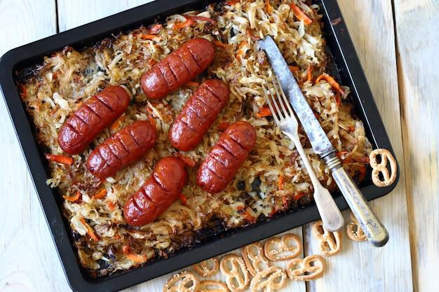 Gebackenes sauerkraut mit würstchen.
