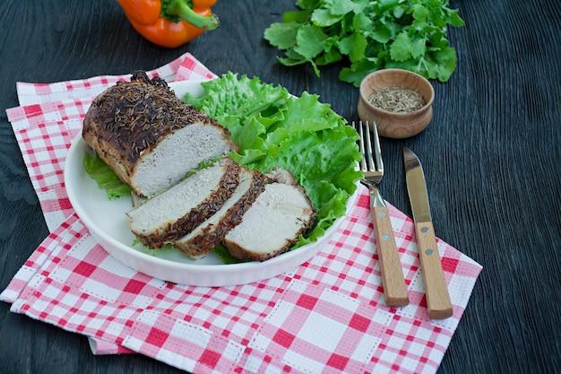 Gebackenes schweinefilet in den gewürzen geschnitten auf einer weißen platte mit grünem salat.