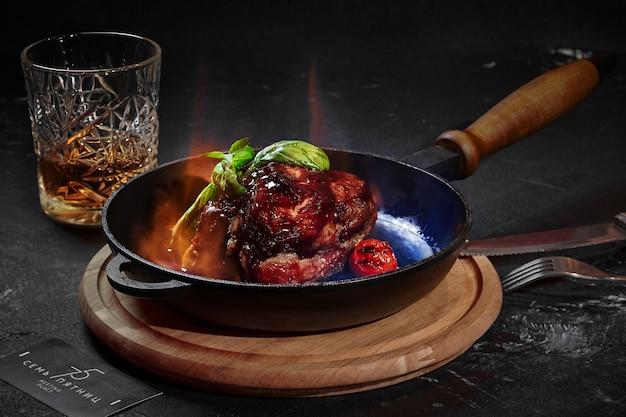 Gebackenes schweinefleisch in barbecue-sauce mit brandy in der pfanne geflammt