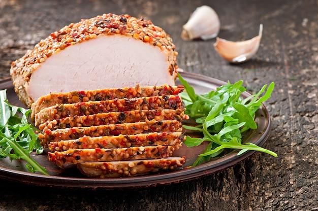 Gebackenes schweinefleisch verziert mit arugulablättern