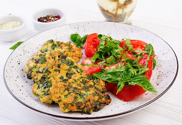 Gebackenes steak, gehacktes hähnchenfilet mit spinat und einer beilage tomatensalat. europäische küche. diätetische lebensmittel.