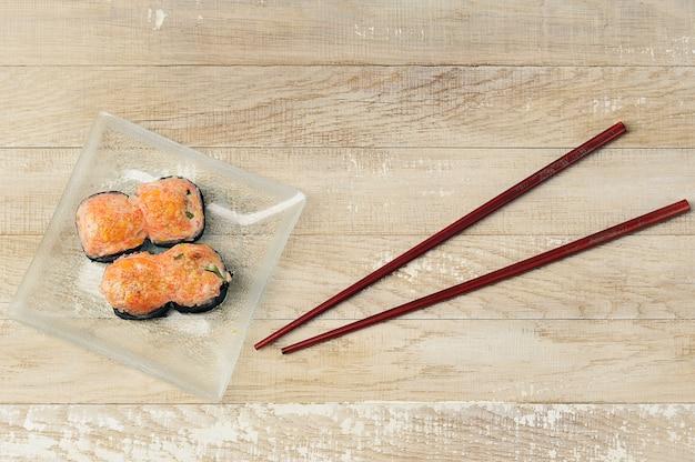Gebackenes sushi auf einem teller mit stäbchen