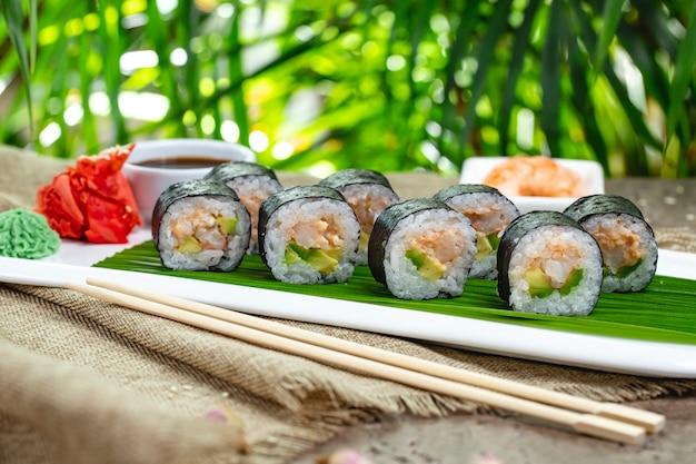 Gebackenes sushi mit wasabi, ingwer und sojasauce auf einem bambusblatt