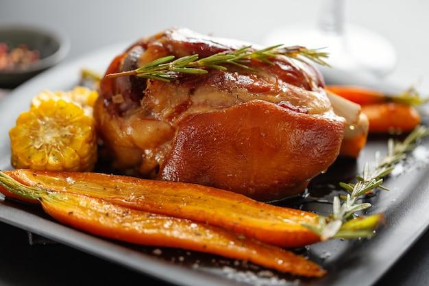 Gebackenes weihnachtsschweinefleisch mit gemüse und gewürzen auf dem teller. nahaufnahme