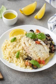 Gebackenes weißes fischfilet mit oliven, tomaten und zitrone